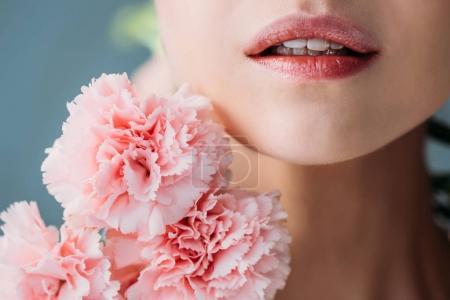 Photo pour Recadrée tir de femme sans maquillage, posant avec un bouquet de fleurs près de son visage - image libre de droit