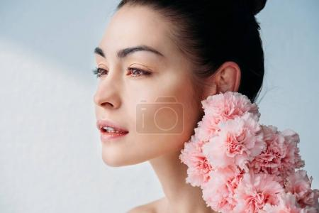 Photo for Portrait shot of beautiful woman with no makeup posing with a bouquet of flowers near her face - Royalty Free Image