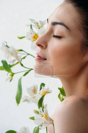 woman with natural makeup posing with lilies