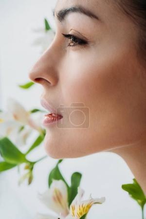 Photo pour Coup de vue de côté de jeune femme douce belle peau posant avec des Lys blancs à l'arrière-plan - image libre de droit