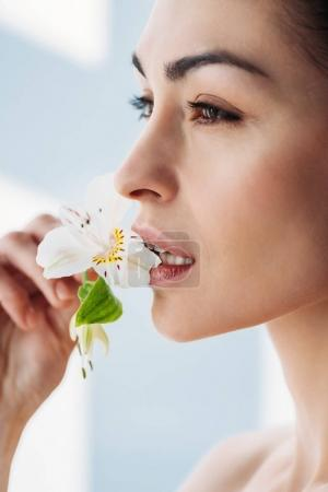 Woman with fresh skin with lily in lips