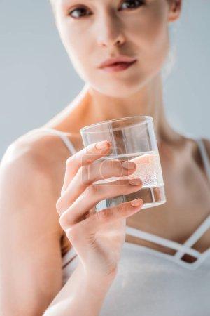 Photo pour Belle jeune femme avec maquillage naturel tenant un verre d'eau et regardant la caméra - image libre de droit