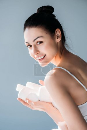 Smiling woman holding cosmetic containers