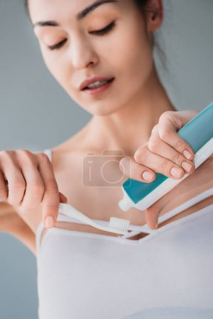 Photo for Young attractive woman with no makeup squeezing toothpaste onto a brush - Royalty Free Image