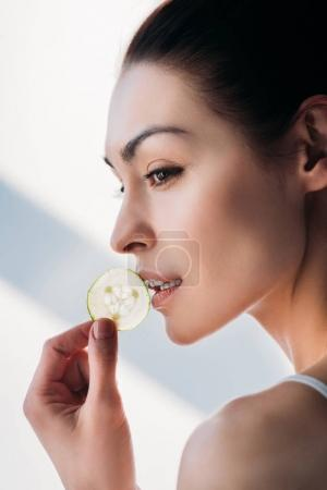 Woman eating slice of cucumber