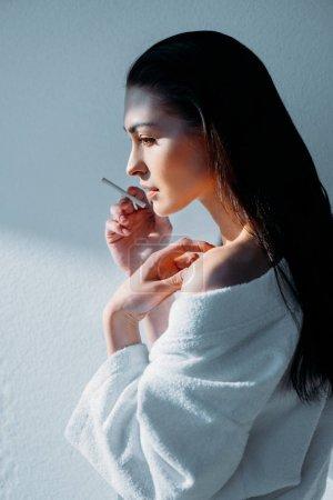 Young woman in bathrobe smoking