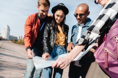 Photo pour Groupe de jeunes amis multiculturels choisir la destination sur la carte ensemble - image libre de droit
