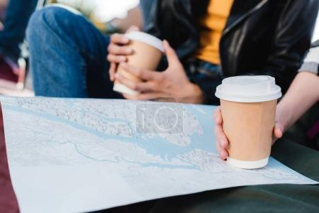 women with map and coffee to go