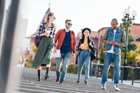 multicultural friends walking on street