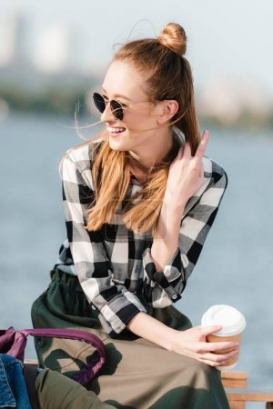 Photo for Portrait of cheerful woman in sunglasses with coffee to go looking away - Royalty Free Image