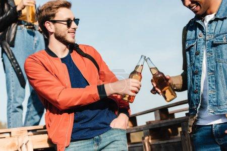 Foto de Vista parcial de hombres multiculturales tintineo alcohol bebidas en manos - Imagen libre de derechos