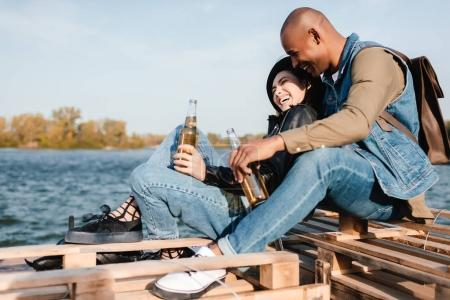 Photo for Side view of multicultural couple with drinks resting together - Royalty Free Image