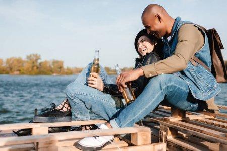 Photo pour Vue latérale d'un couple multiculturel avec boissons au repos ensemble - image libre de droit