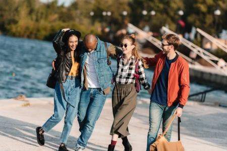 multicultural friends walking on pier