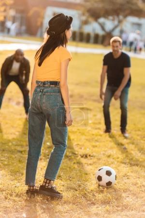 Foto de Amigos multiculturales jugando al fútbol juntos en el Parque - Imagen libre de derechos