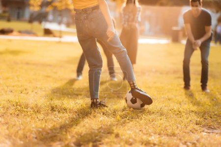 Friends playing soccer in park