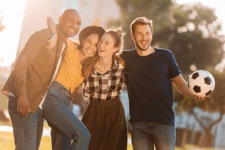 Photo pour Portrait d'amis multiculturels heureux avec ballon de football s'embrassant dans le parc - image libre de droit