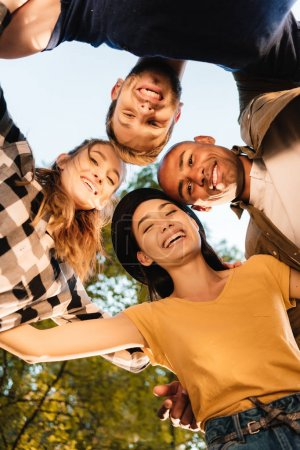 Photo for Bottom view of happy multicultural friends standing in circle - Royalty Free Image