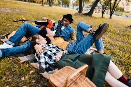 Foto de Grupo multicultural de amigos descansando en manta en el Parque - Imagen libre de derechos