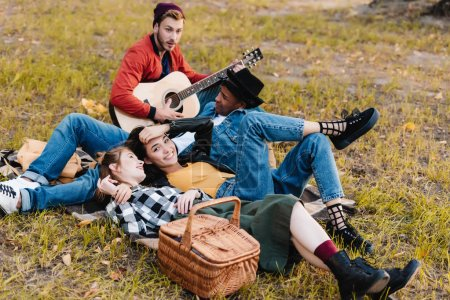 Photo for Group of happy multicultural friends resting in park together - Royalty Free Image