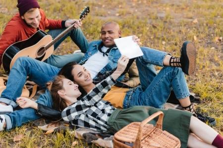 Photo pour Femmes souriantes multiculturelles prenant selfie tandis que les hommes se reposant sur la couverture près dans le parc - image libre de droit