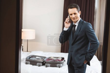 Businessman talking on phone in hotel room