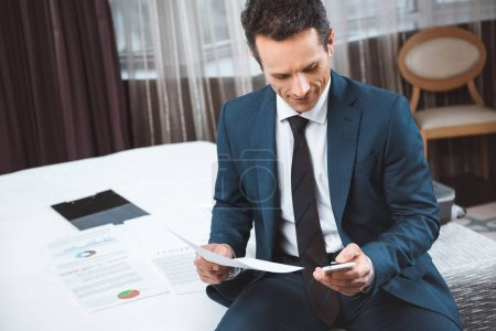businessman holding paperwork and using smartphone