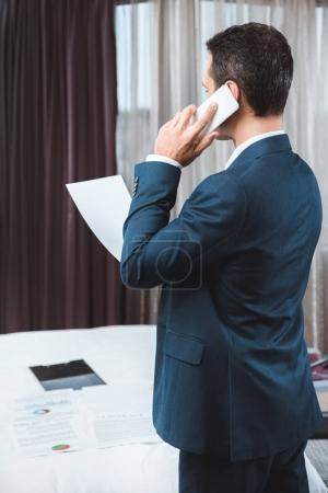 businessman holding paperwork and talking on phone