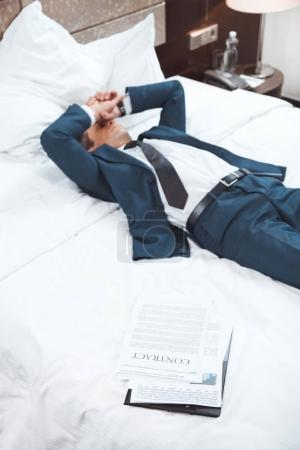 Exhausted businessman lying on bed