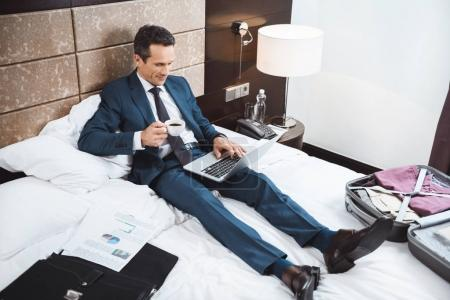 businessman on bed working with laptop