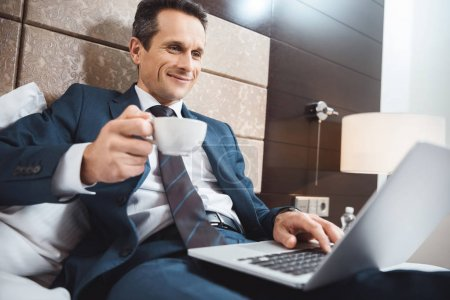 businessman on bed with laptop and coffee