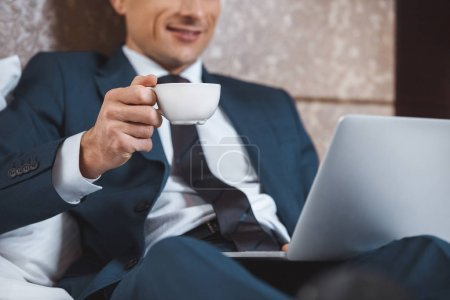 Photo for Young businessman in formal suit using his laptop and holding cup of coffee, while sitting on bed in hotel room - Royalty Free Image