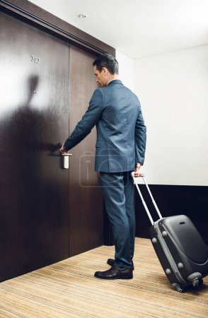 Photo for Businessman in formal suit holding a suitcase and opening hotel room door - Royalty Free Image