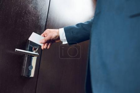 Photo for Cropped shot of businessman in suit opening a hotel room door with card - Royalty Free Image