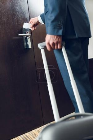 businessman with suitcase opening door