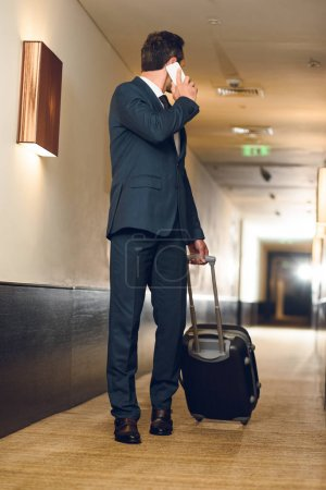 businessman with suitcase talking on phone