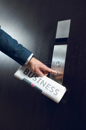 businessman with newspaper calling elevator