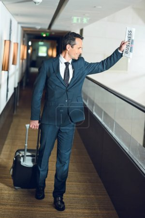 businessman walking in hotel corridor with suitcase