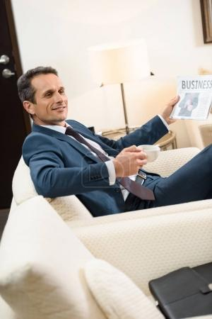 Businessman with newspaper and coffee