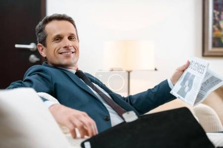Photo for Smiling businessman in formal suit sitting in armchair with newspaper - Royalty Free Image