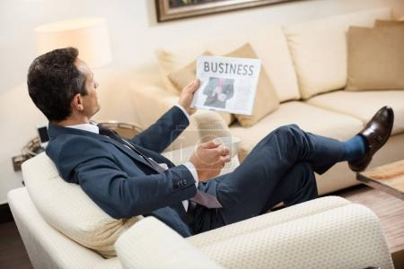 businessman reading newspaper with coffee