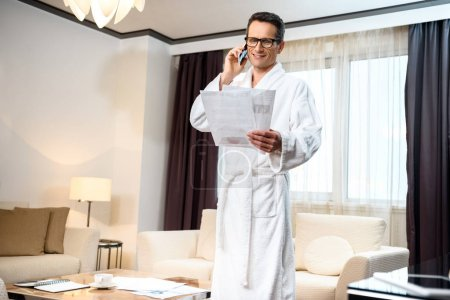 Businessman in bathrobe talking on phone
