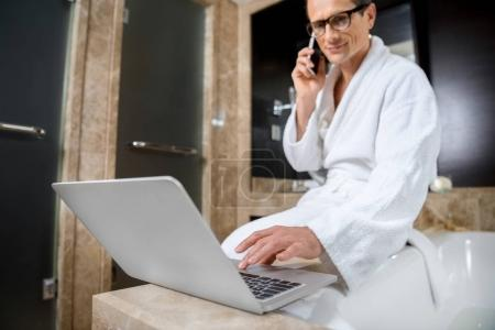 Businessman in bathrobe using laptop