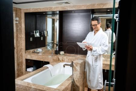 Businessman in bathrobe working with tablet