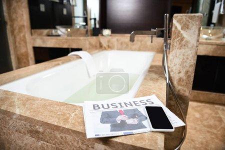 Business newspaper on bathtub