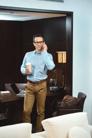businessman with coffee talking on phone