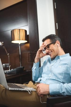 businessman in headphones using laptop