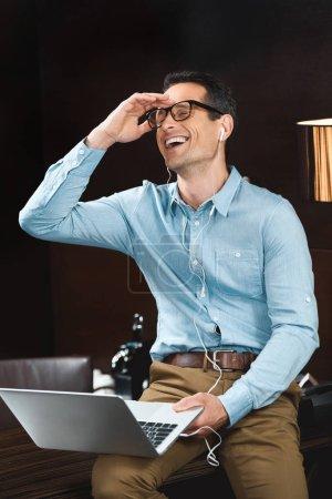 Laughing businessman in headphones using laptop