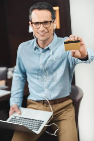 businessman holding credit card and laptop