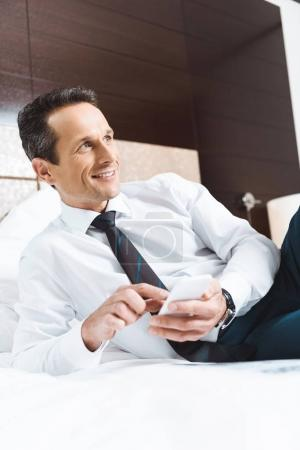 Businessman on bed using smartphone